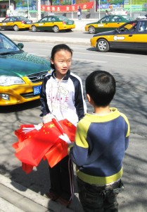 Дети продают флажки в очереди на автобус