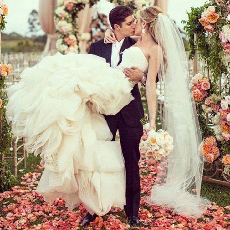 Жених держит невесту на руках, жених и невеста целуются