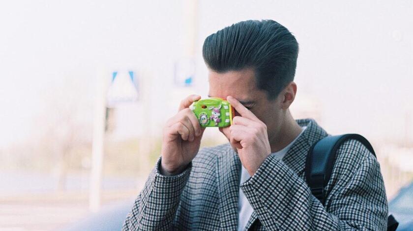парень фотографирует на детский фотоаппарат